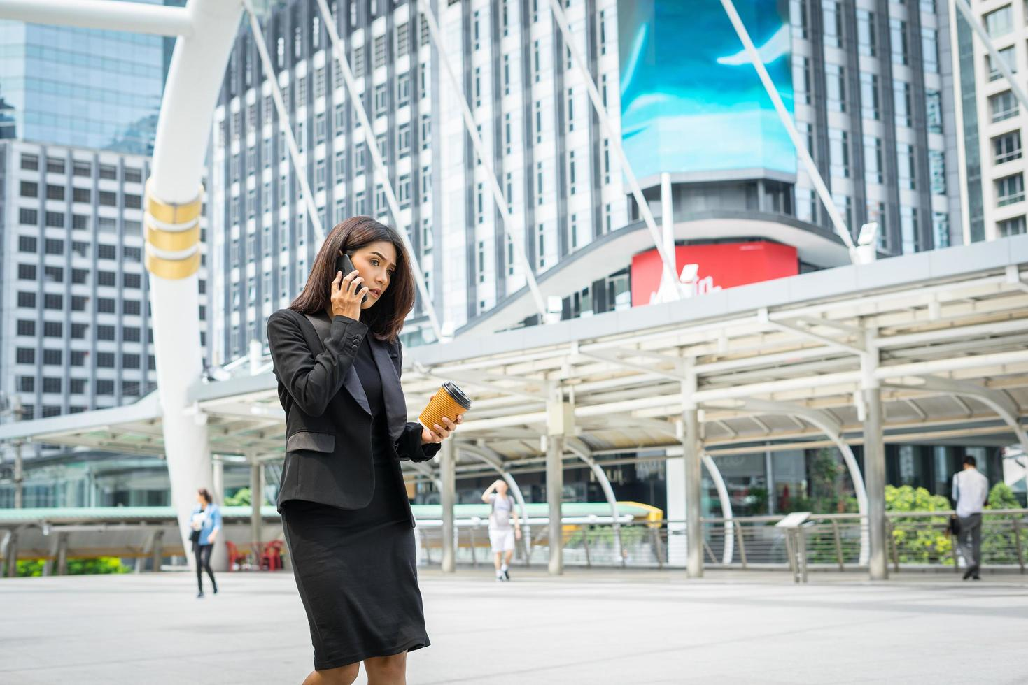 Business woman using phone with coffee walking on the street photo