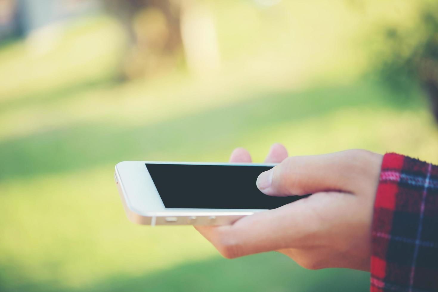 Mujer joven con un teléfono inteligente al aire libre en el parque foto