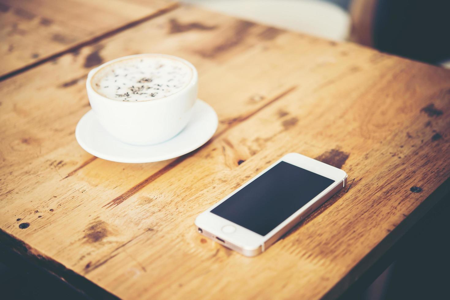 A cup of coffee and smartphone on wooden table in cafe photo