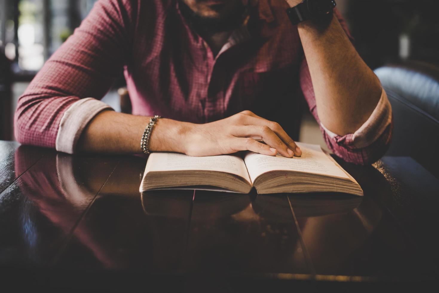 Joven hipster barbudo leyendo un libro en un café foto