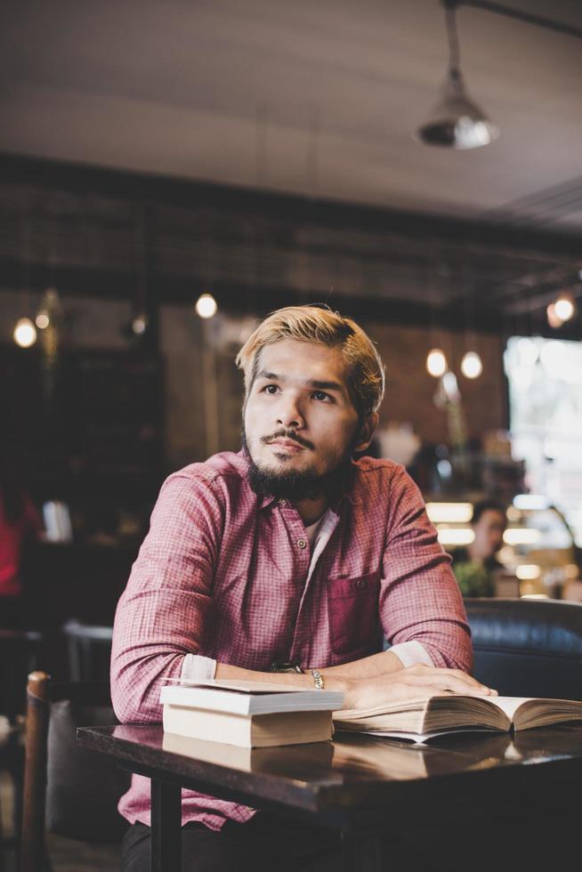 hipster barbudo libro de lectura en la cafetería. foto