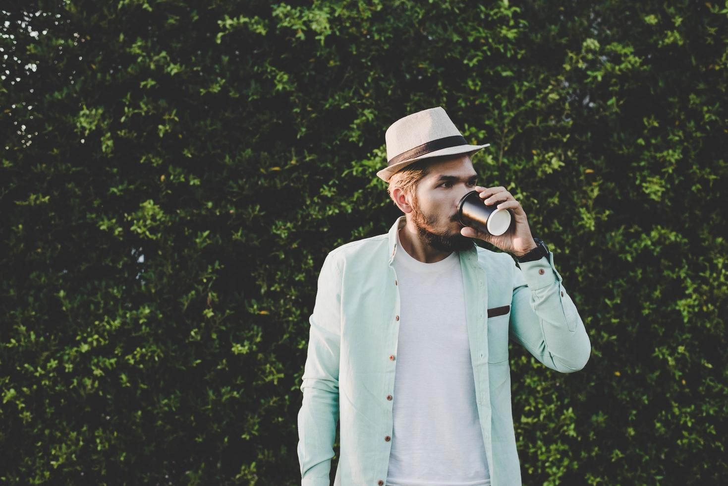 Happy hipster man holding hot coffee photo