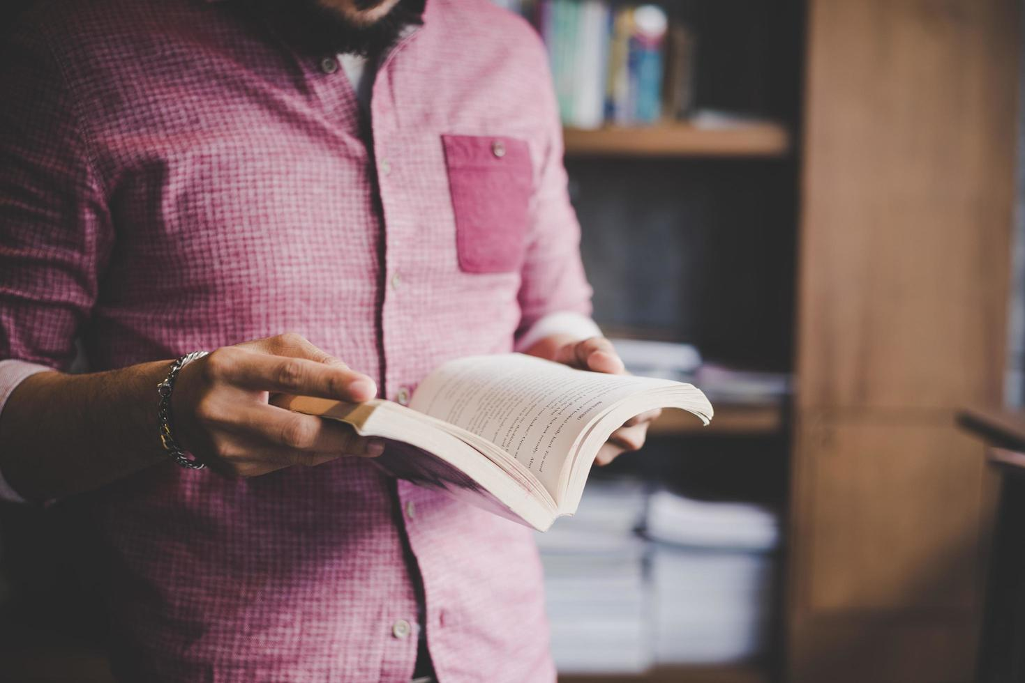 Young hipster man reading book in a library photo