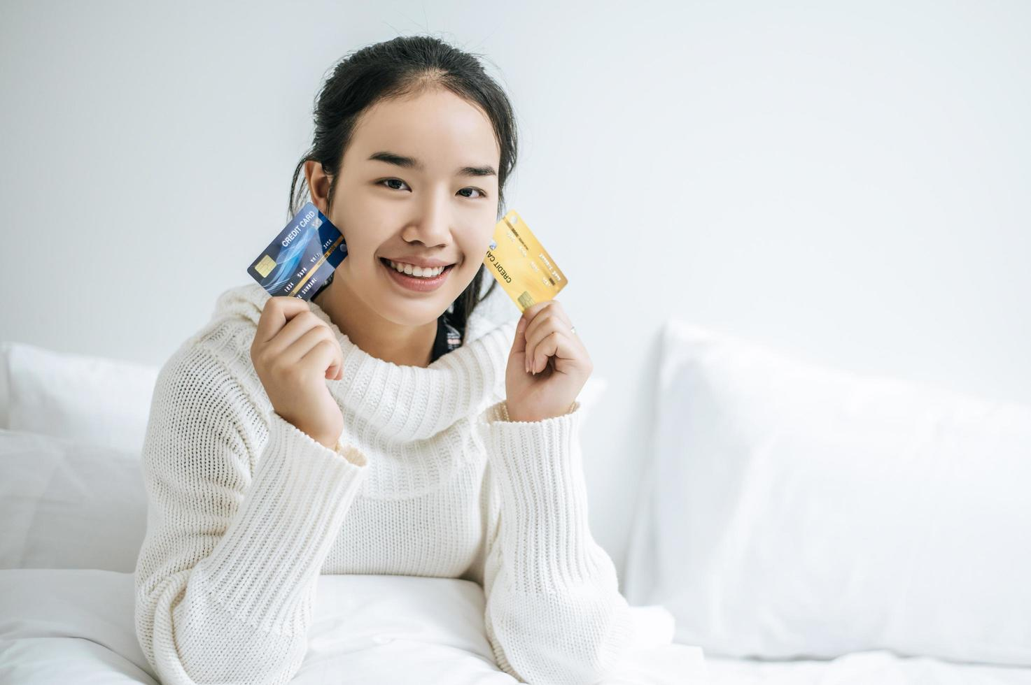 Young woman with a credit card smiling on bed photo