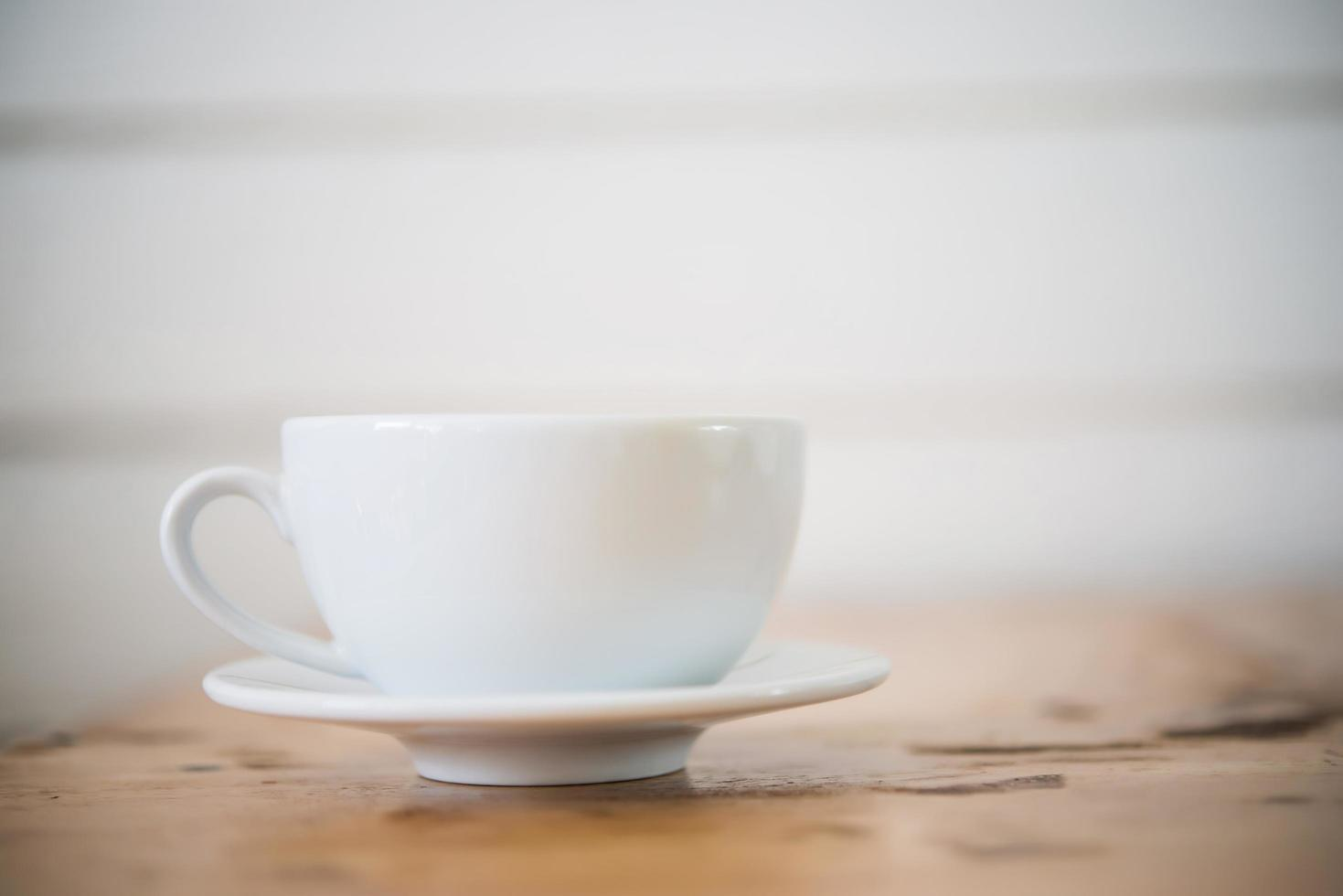 A cup of coffee on wooden table in cafe photo