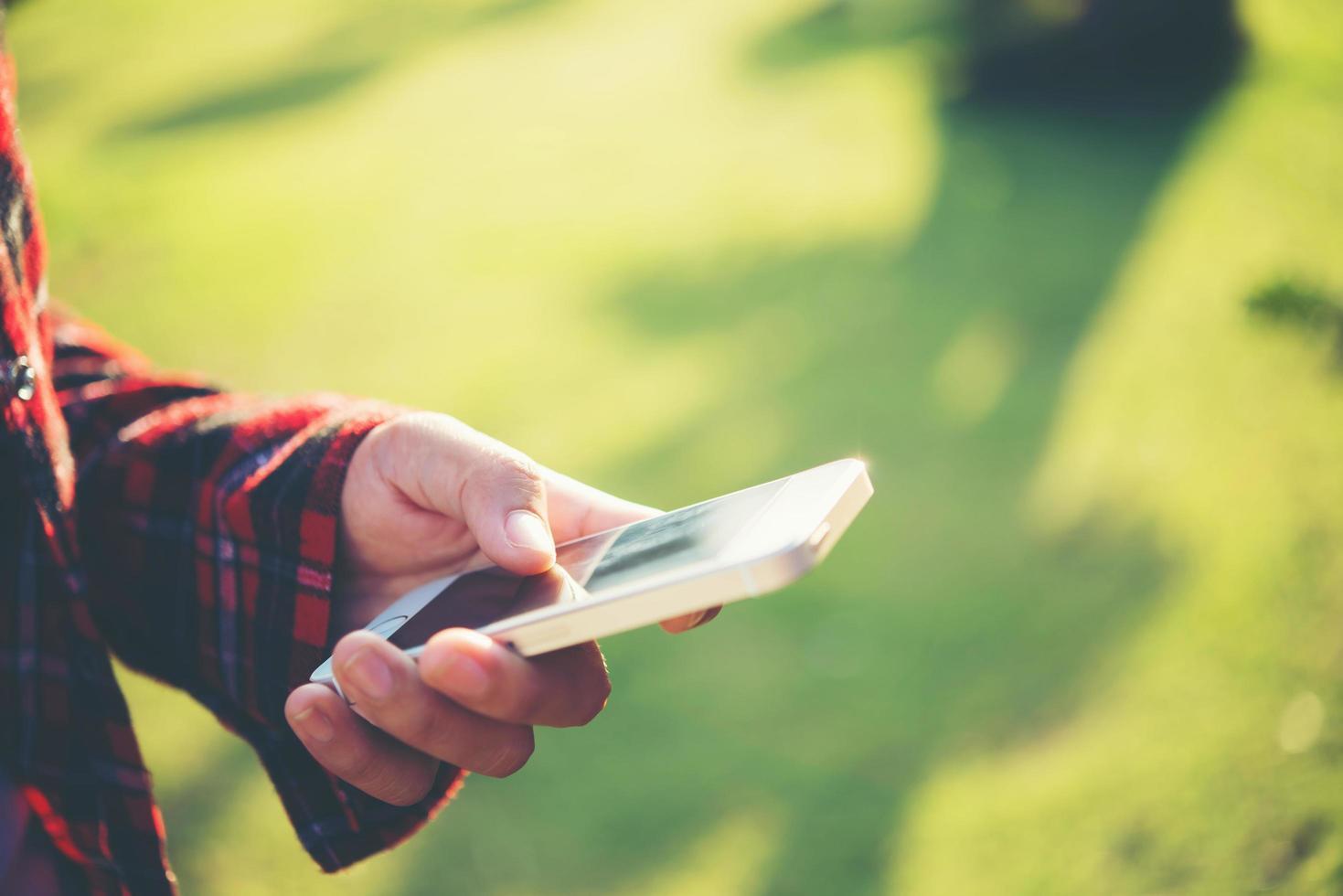 Mujer joven con un teléfono inteligente al aire libre en un parque foto