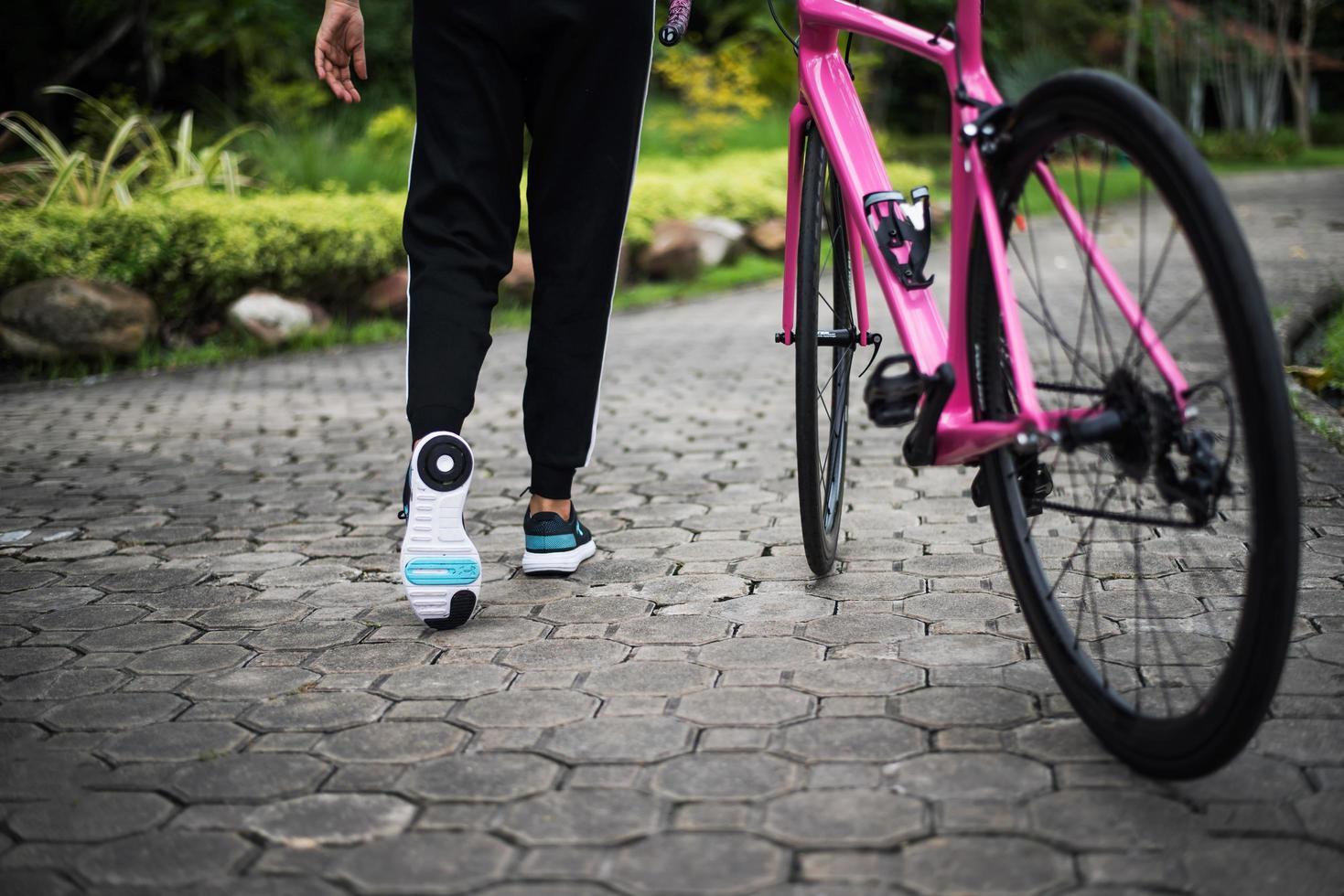 Primer plano de la parte trasera de la mujer con bicicleta de carretera en el parque foto