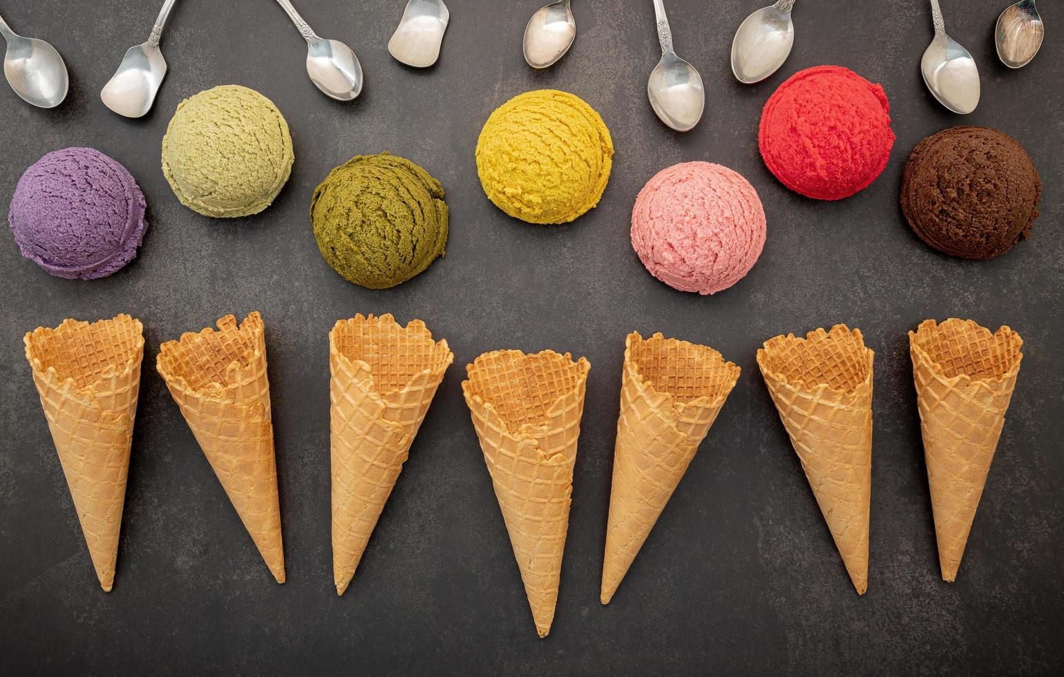 Various of ice cream flavors in scoops with spoons photo