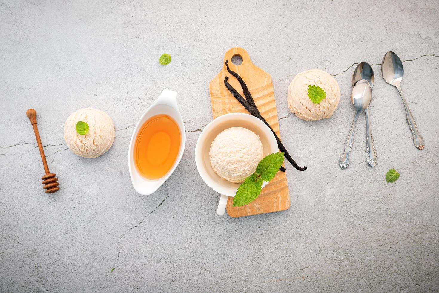 Vanilla ice cream flavor in bowl with vanilla pods setup on concrete background photo