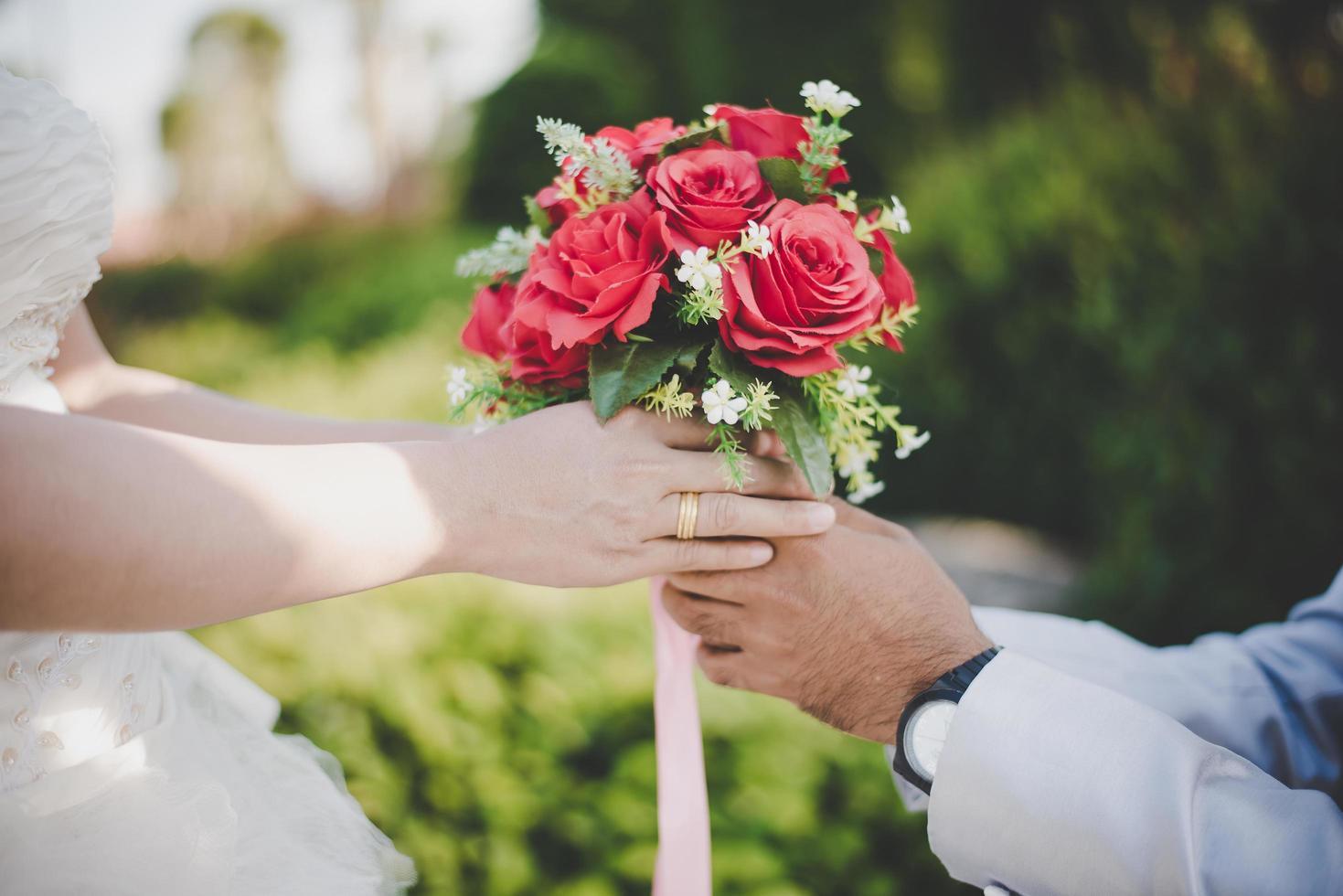 El novio le da un ramo a la novia con fondo de naturaleza. foto