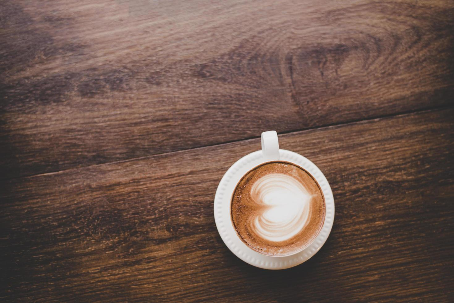 Top view of vintage latte art coffee with heart shape on wooden table photo