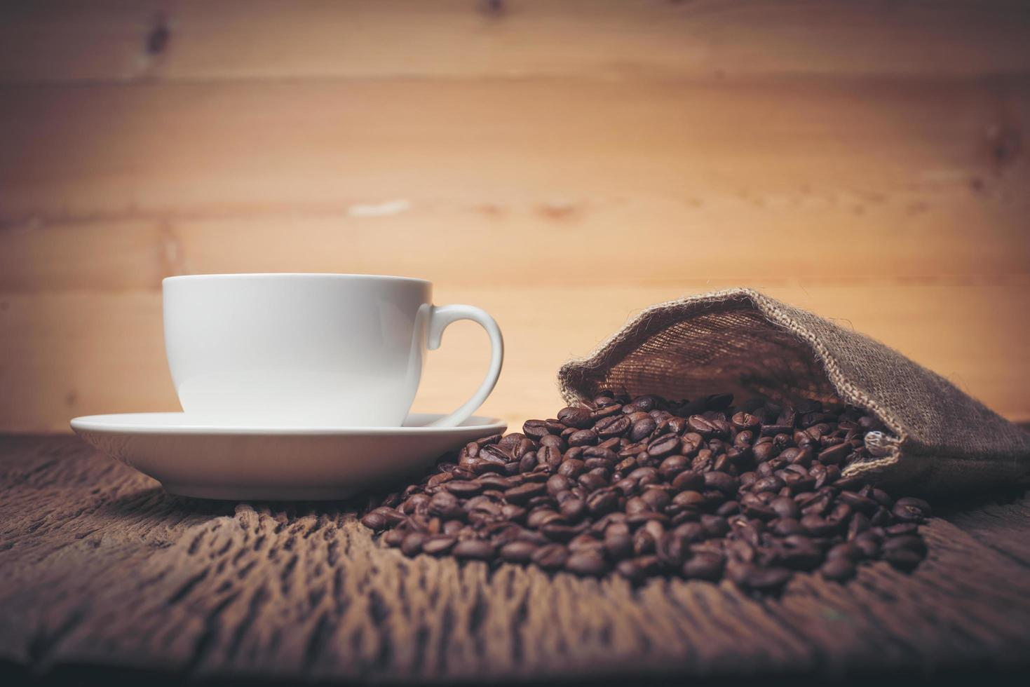 Taza de café con granos de café en una mesa de madera foto