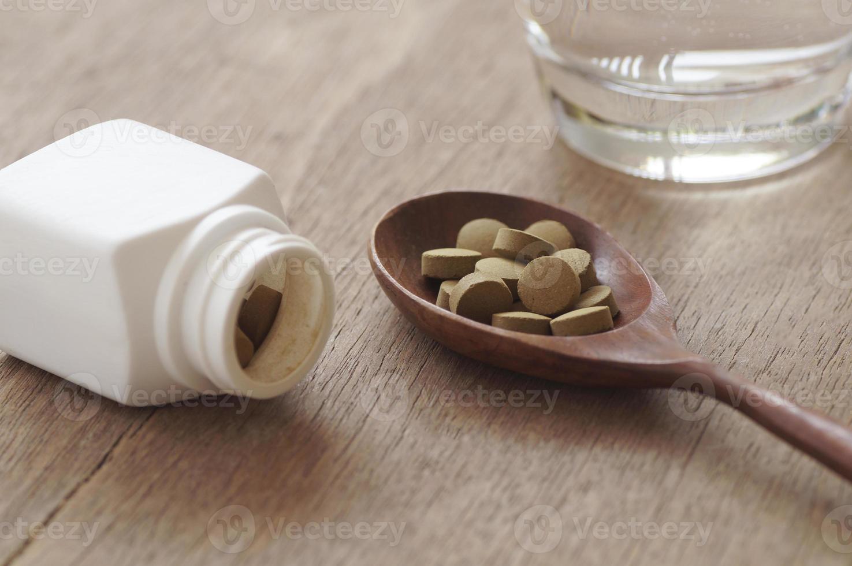 Medicina herbaria en pastilla sobre mesa de madera foto