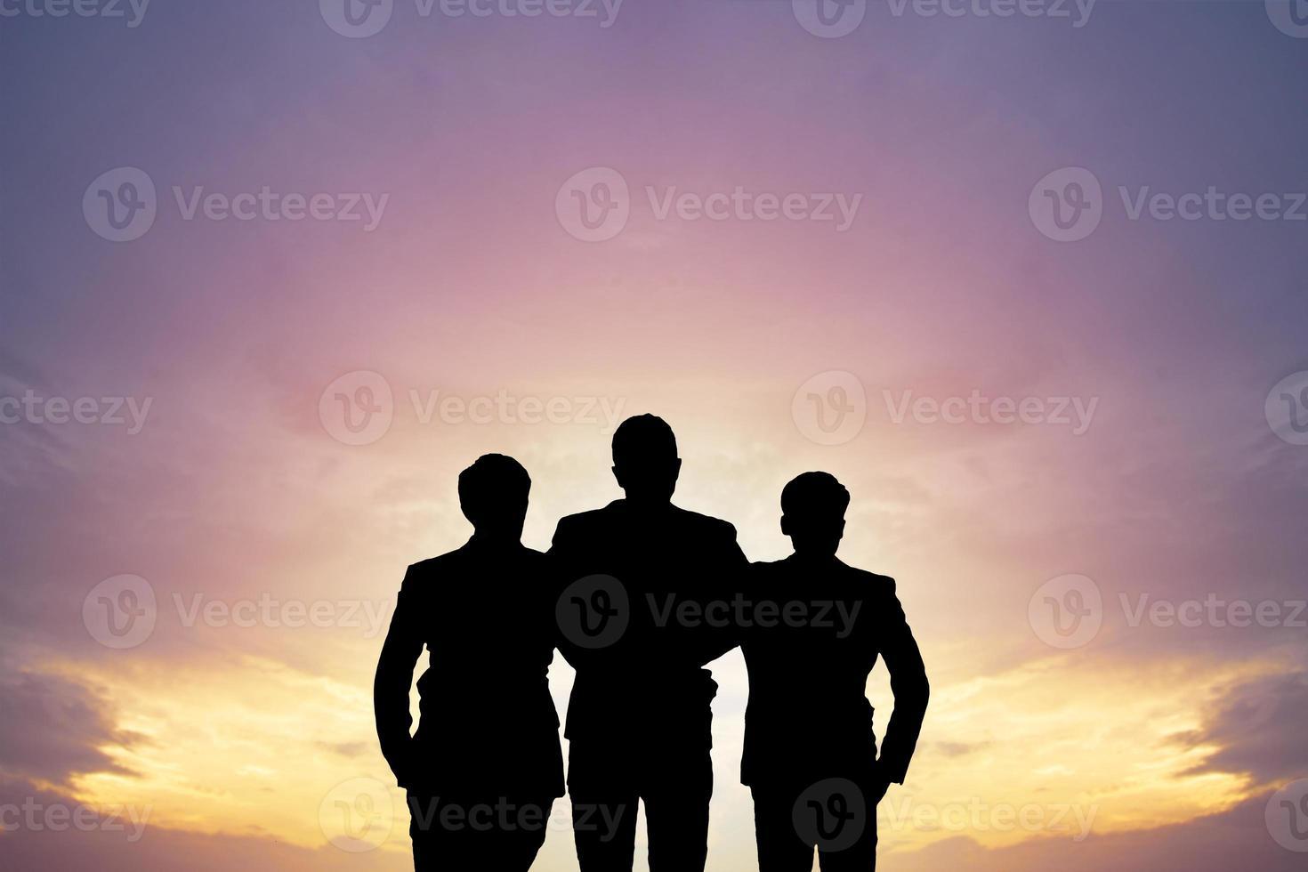 silueta de tres personas en la puesta del sol foto