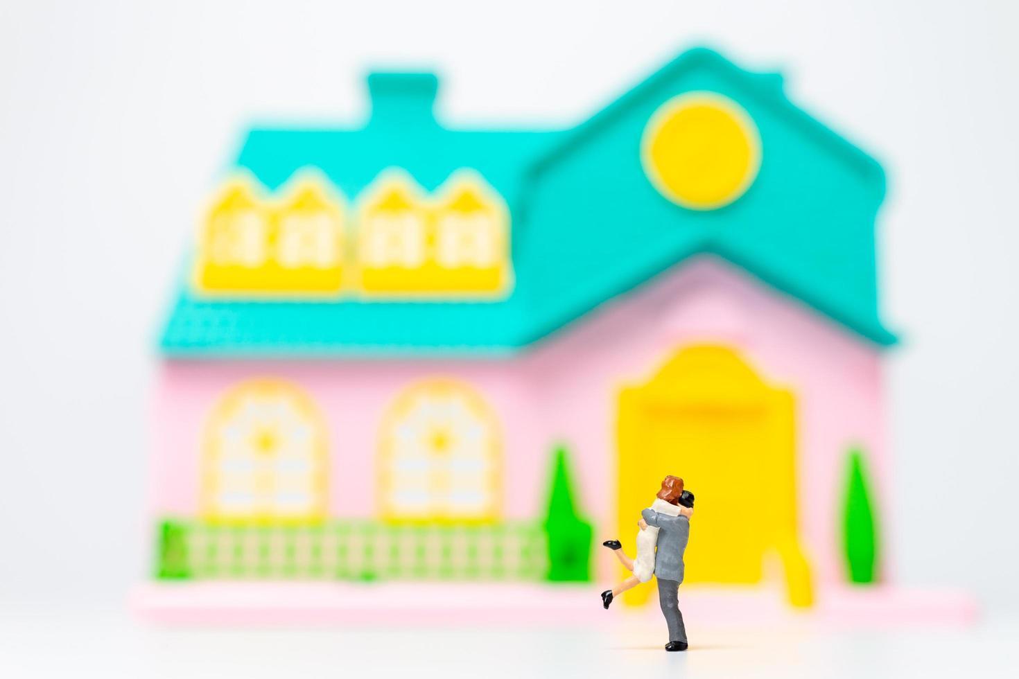 dos figuras en miniatura de personas abrazándose frente a una casa foto