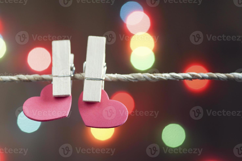 dos alfileres de ropa con corazones rojos en la cuerda foto