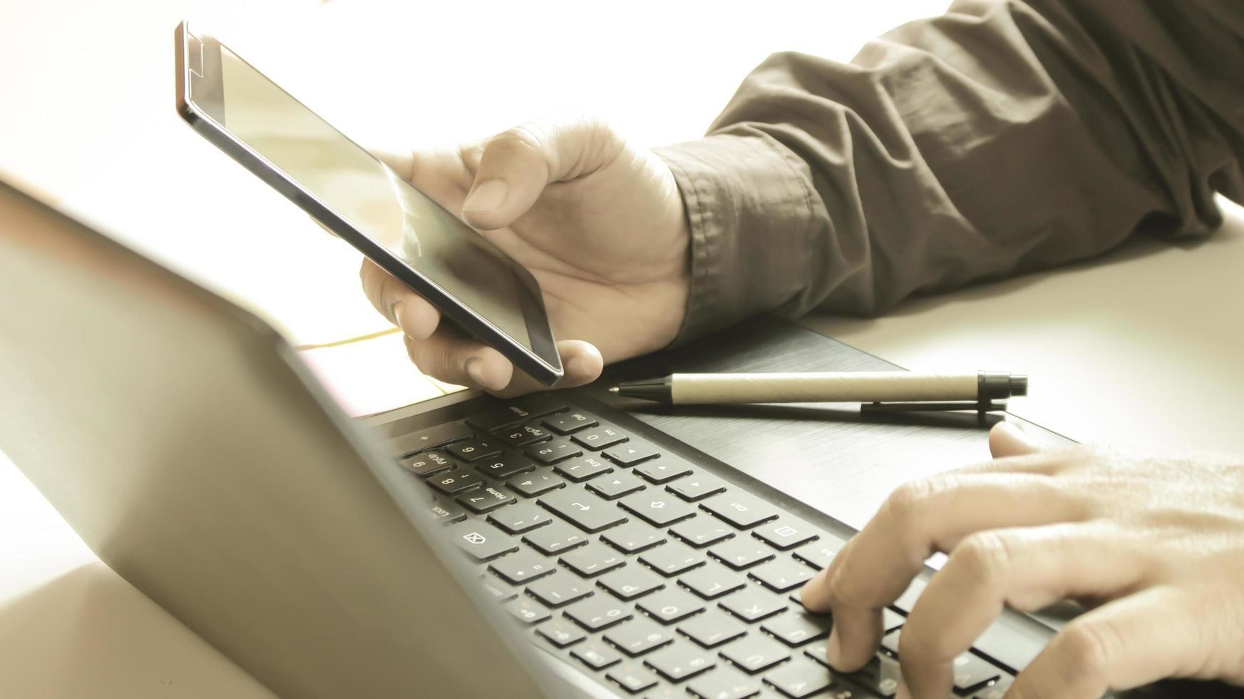 profesional sosteniendo el teléfono y escribiendo en la computadora foto