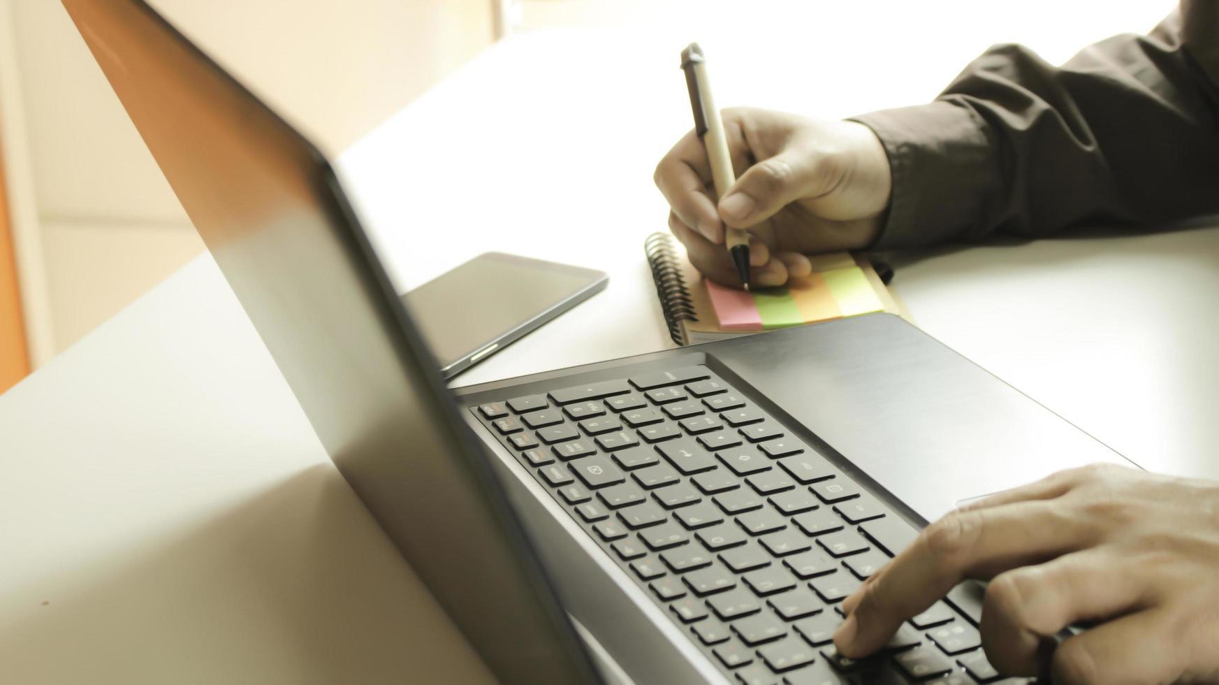 persona tomando notas desde la computadora portátil foto