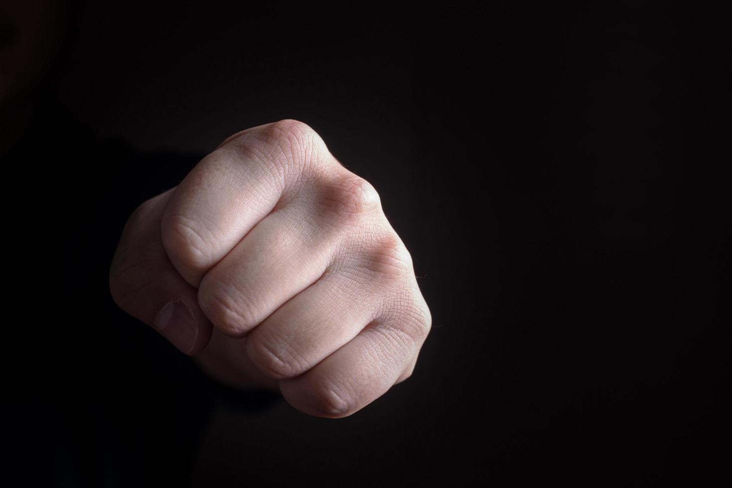 Puño de puño de mano sobre fondo negro foto