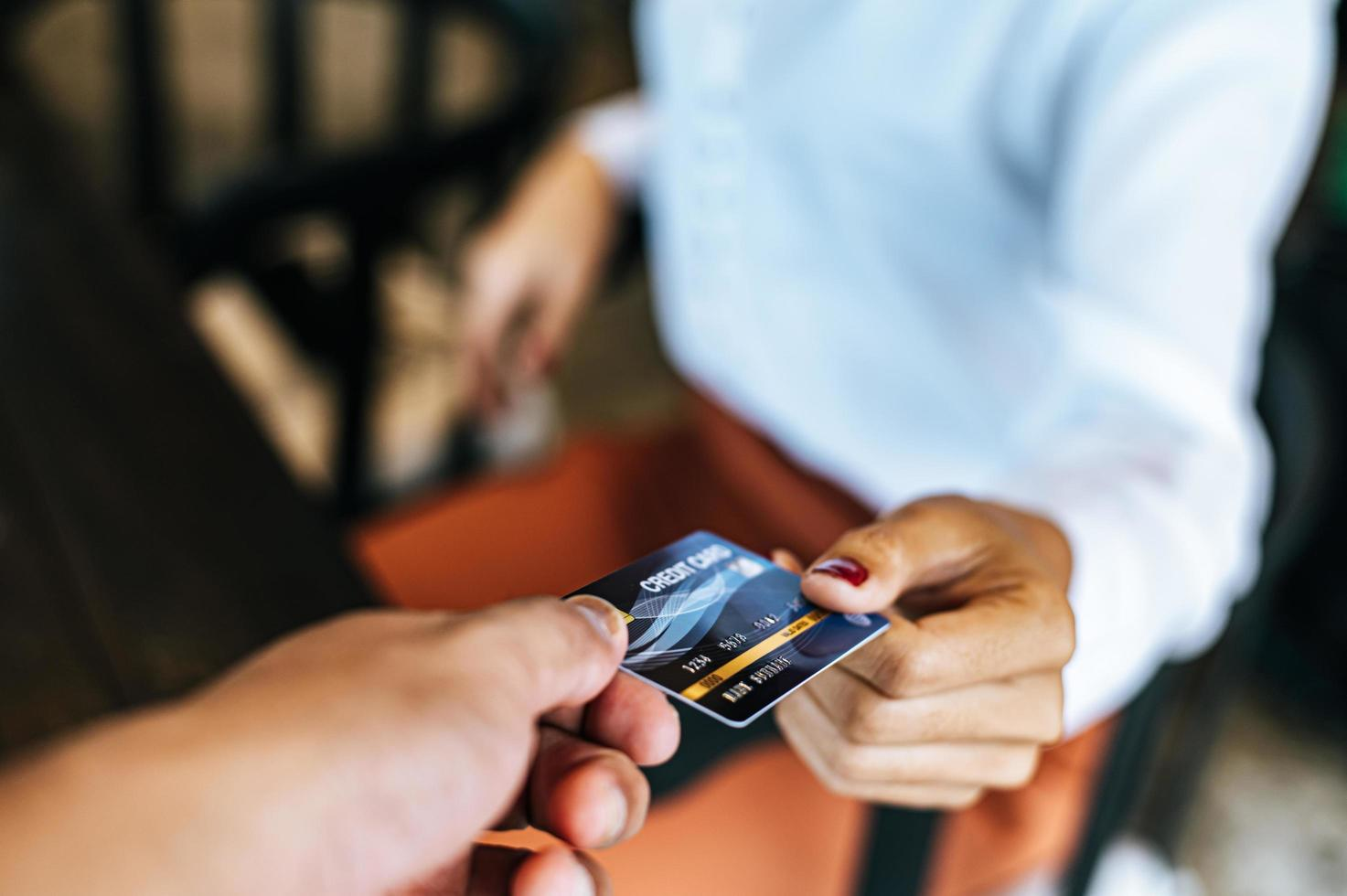 Woman submitting credit card to pay for goods photo