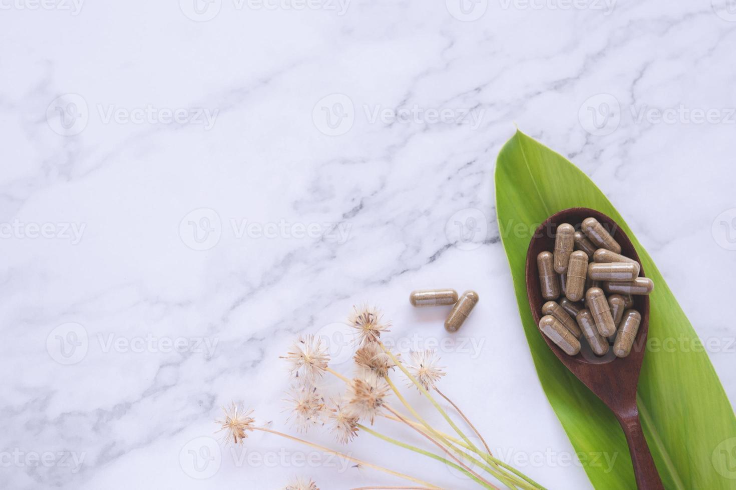 Medicina herbaria en cápsulas en cuchara de madera con hoja verde sobre mármol blanco foto