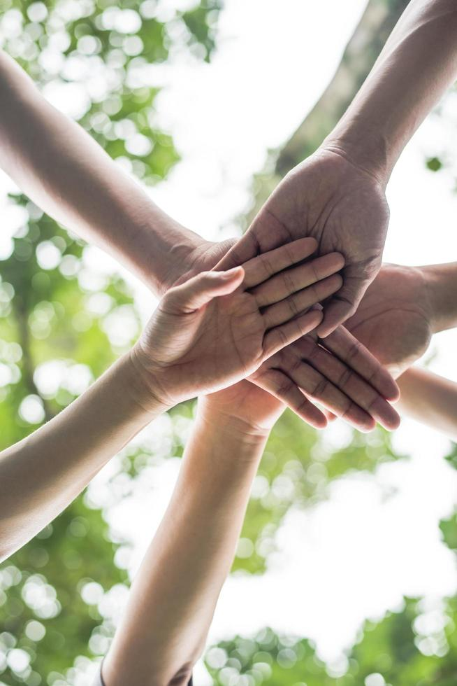 Close-up of a team of students with their hands together photo