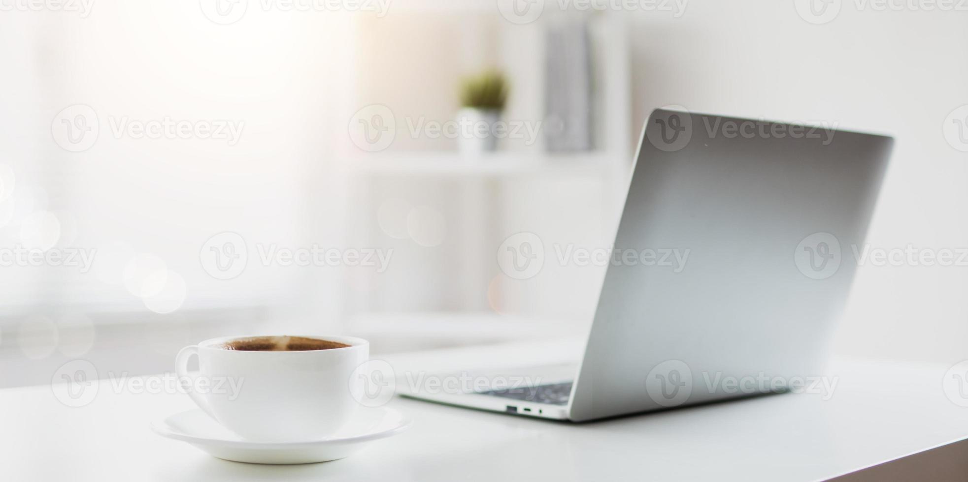 taza de café en la mesa de trabajo con laptop foto