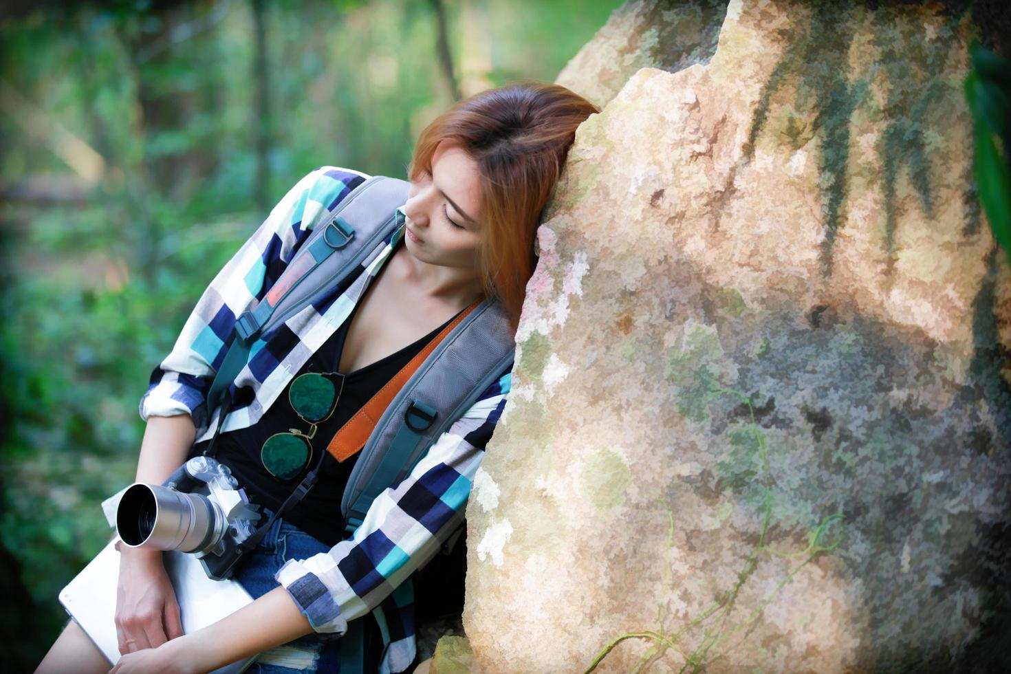 Traveler woman tried and resting on a big rock in a forest photo