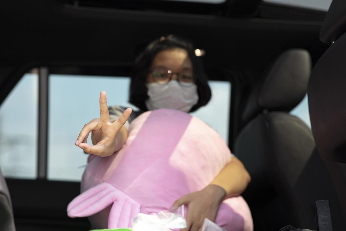 Chica joven con una máscara que muestra un signo v o un signo de la paz durante el covid-19 foto