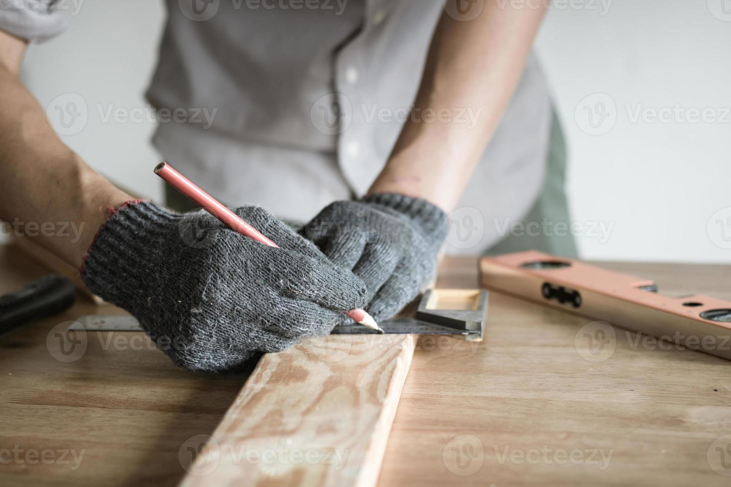Carpenter measuring wood with pencil photo