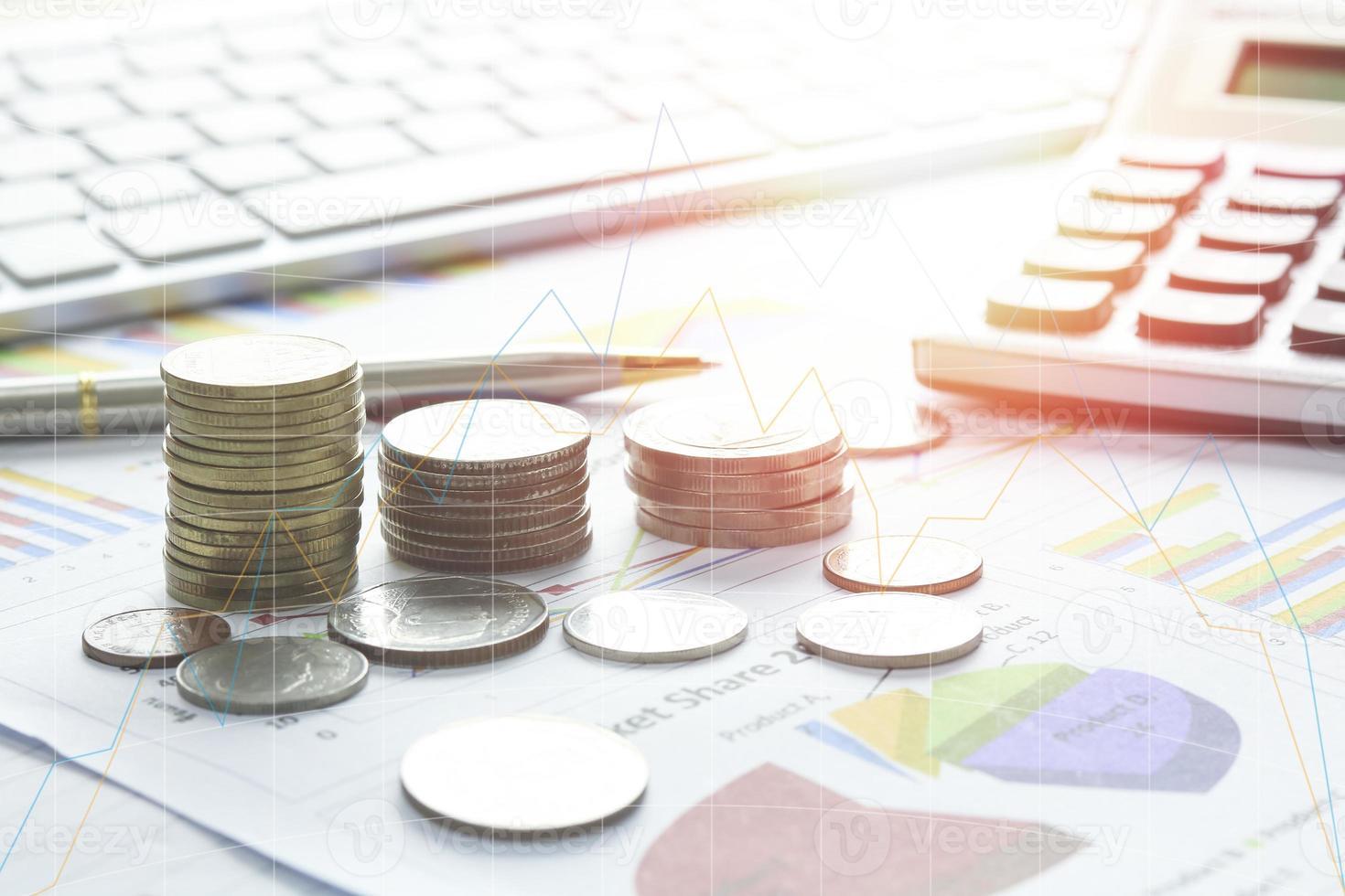 monedas en un escritorio con gráficos y calculadora foto
