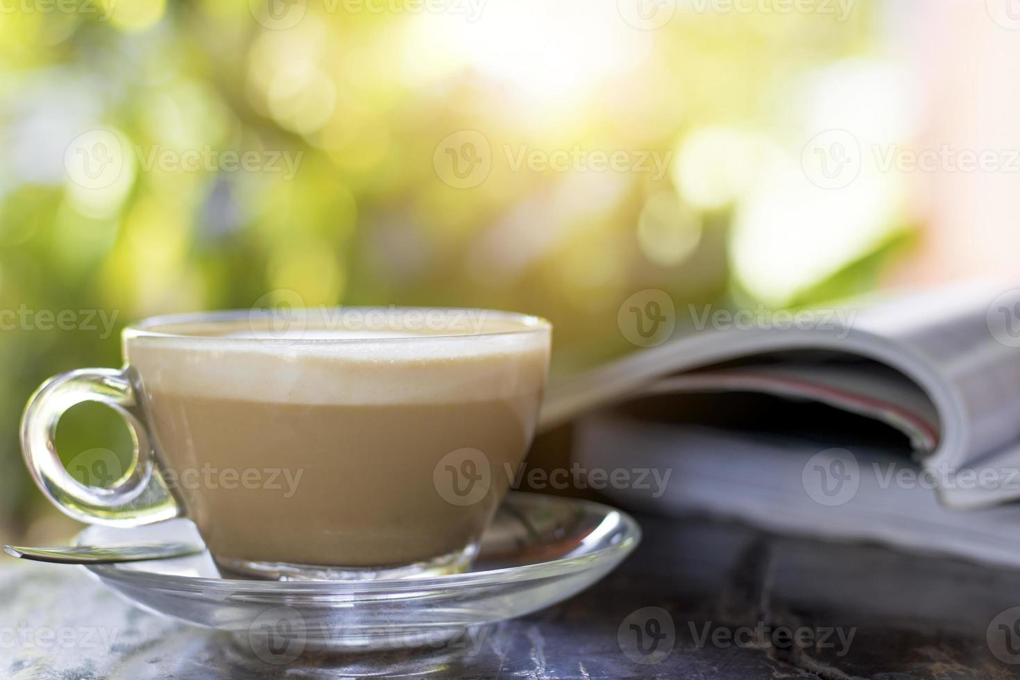 Hot coffee on a table with book photo