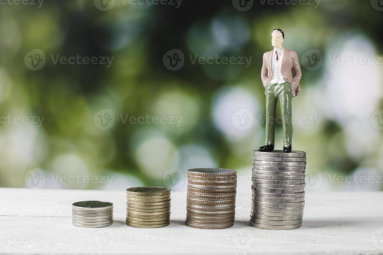 figurilla de persona de negocios de pie sobre pilas de dinero foto