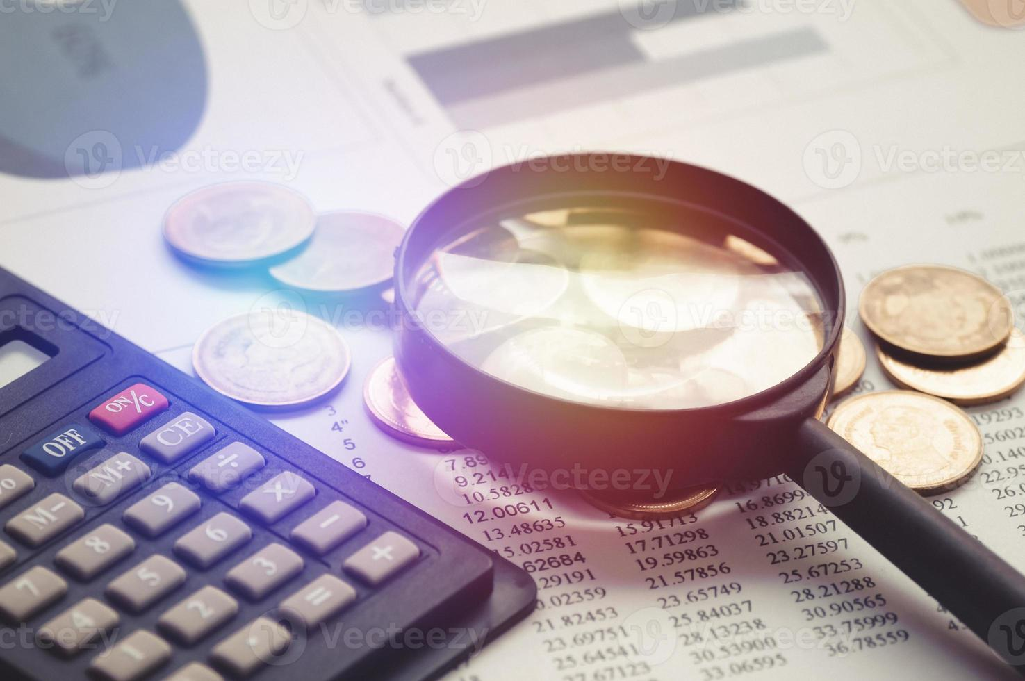 Magnifying glass and pile of coin money photo