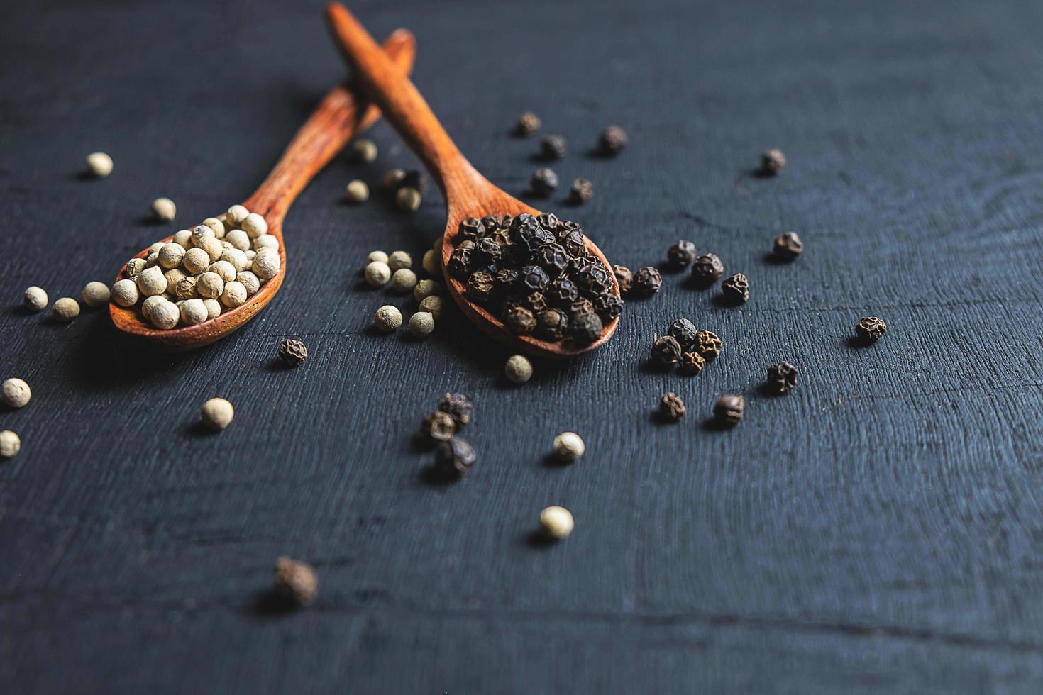 granos de pimienta en cucharas foto