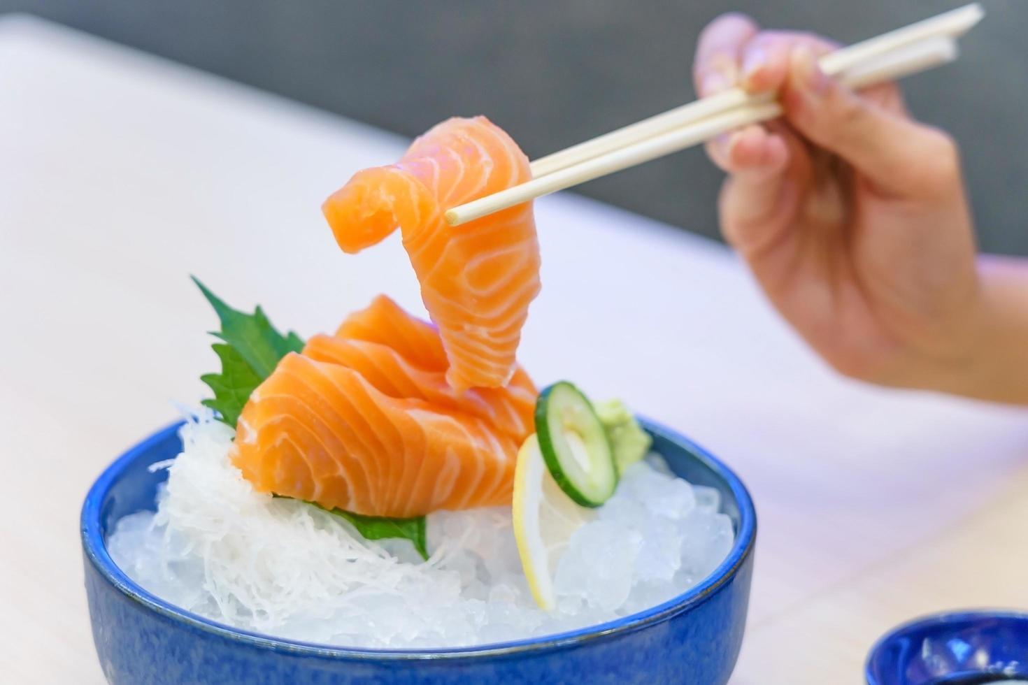 Mano sujetando sashimi de salmón con palillos foto