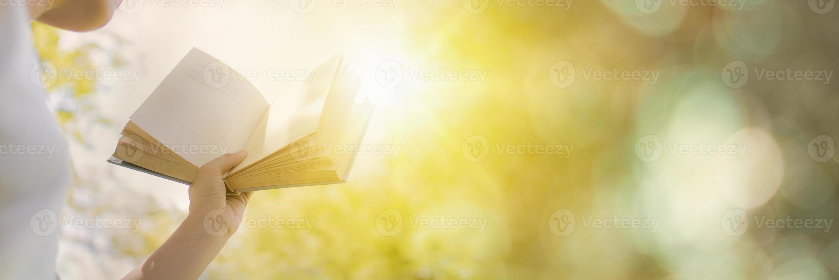 Person holding book opening with sunshine photo