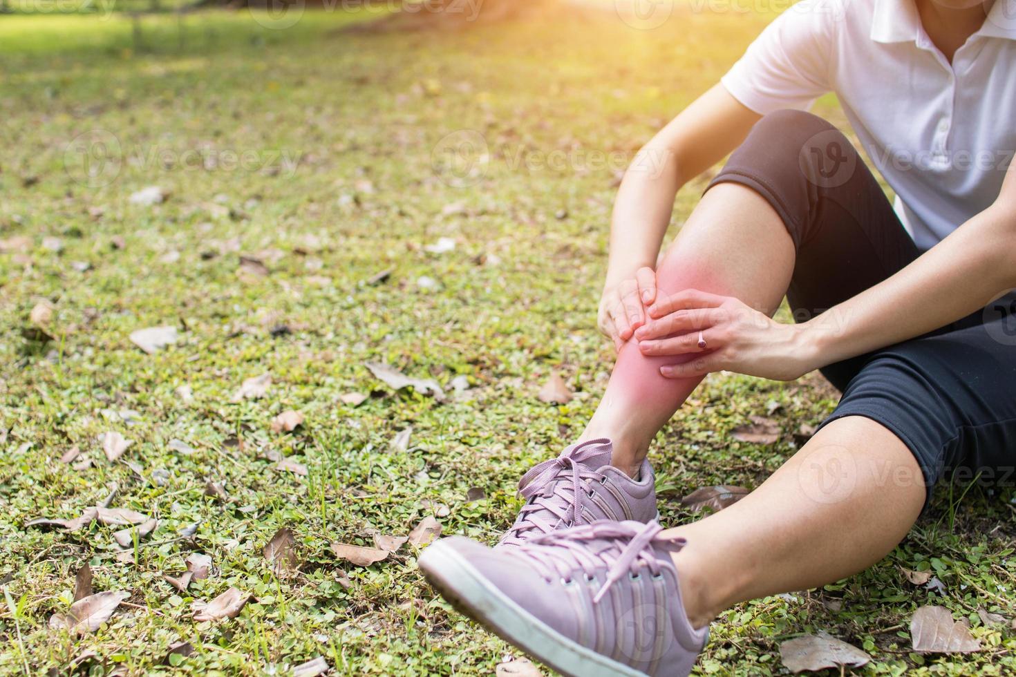 mujer tiene dolor de pierna en el parque foto