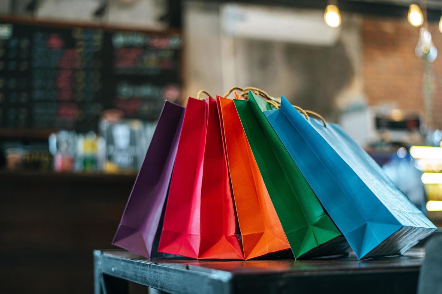 bolsas de papel de colores colocadas sobre la mesa foto