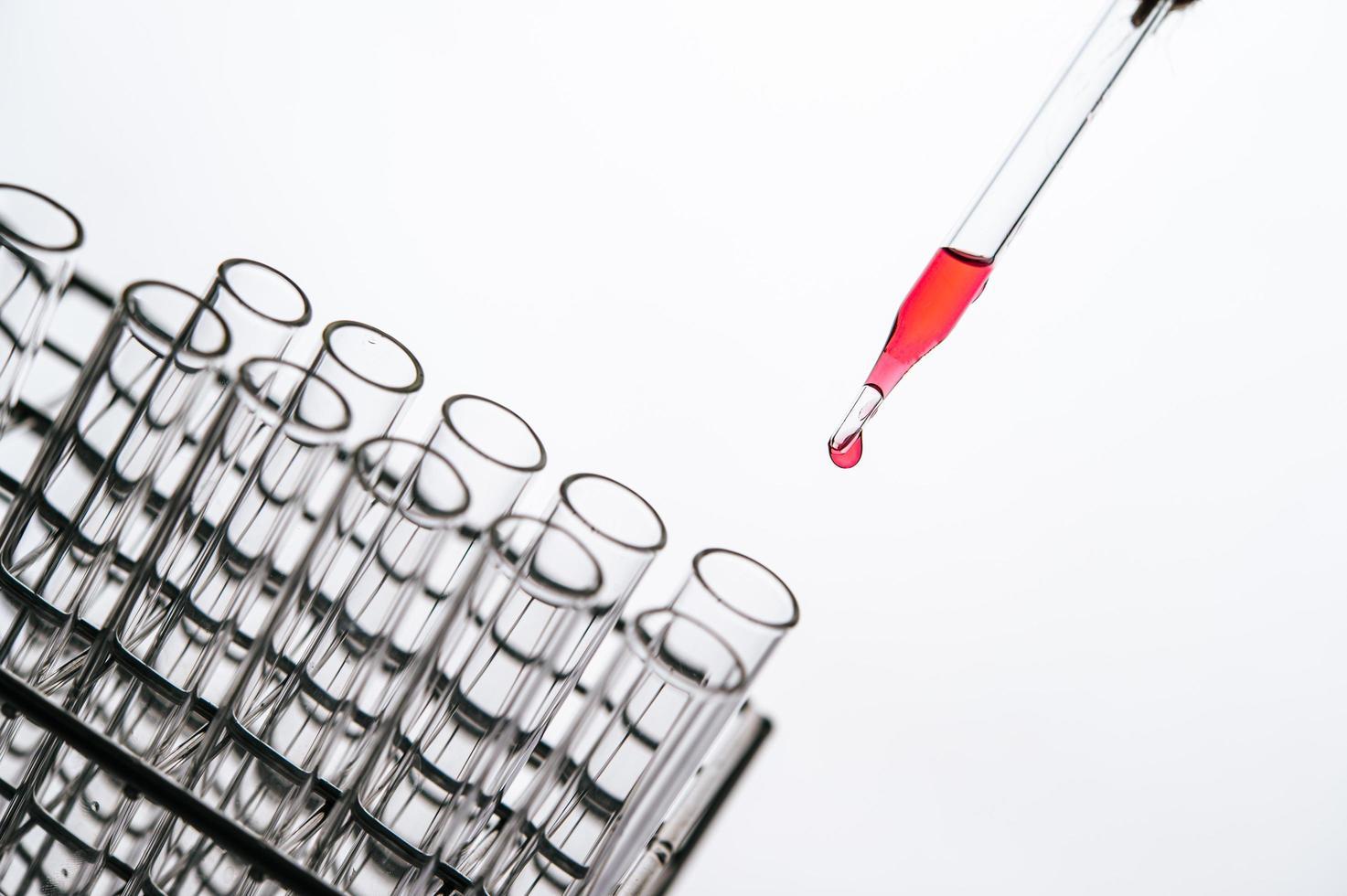 productos químicos rojos caídos en un vaso de precipitados foto