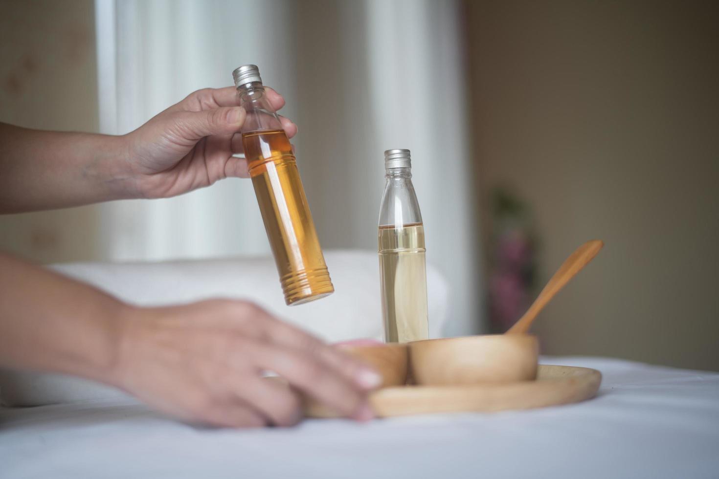 Mano sosteniendo una botella de aceite esencial y tratamientos de spa. foto