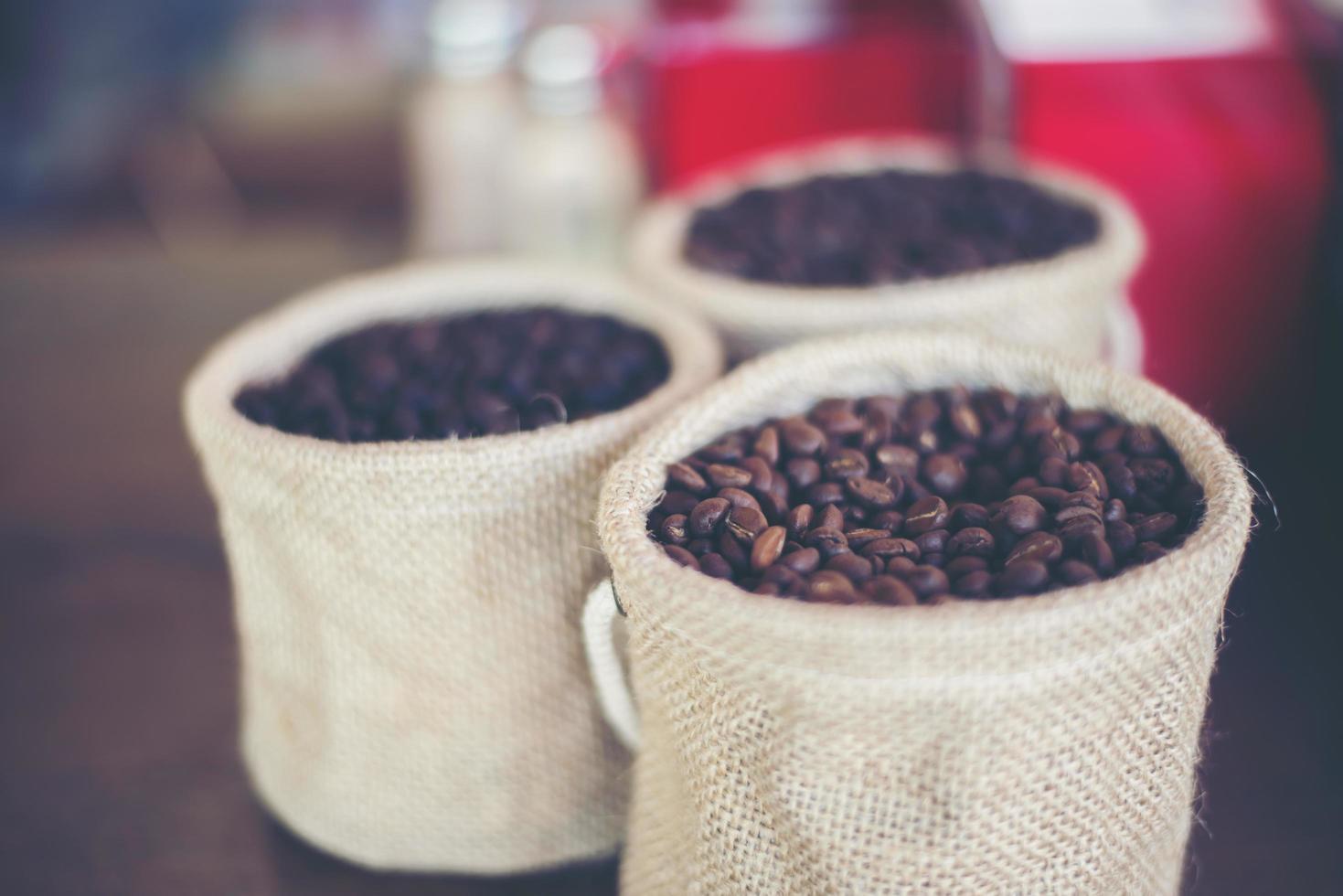 Saco de granos de café sobre fondo de madera foto