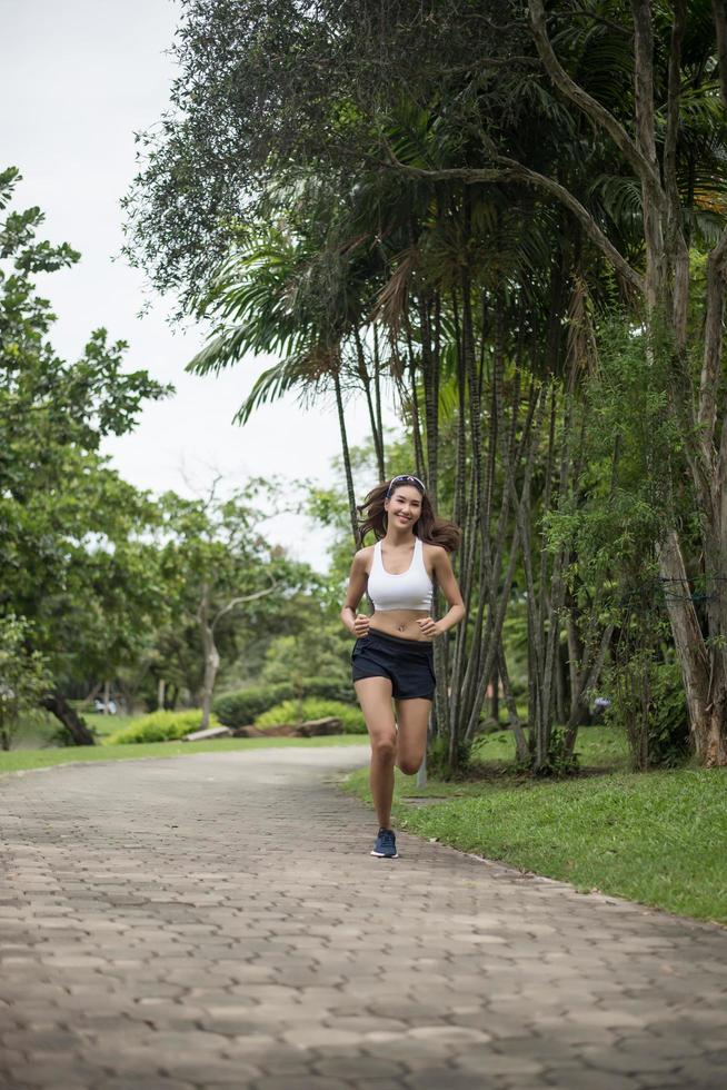 Young sporty woman running in the park photo