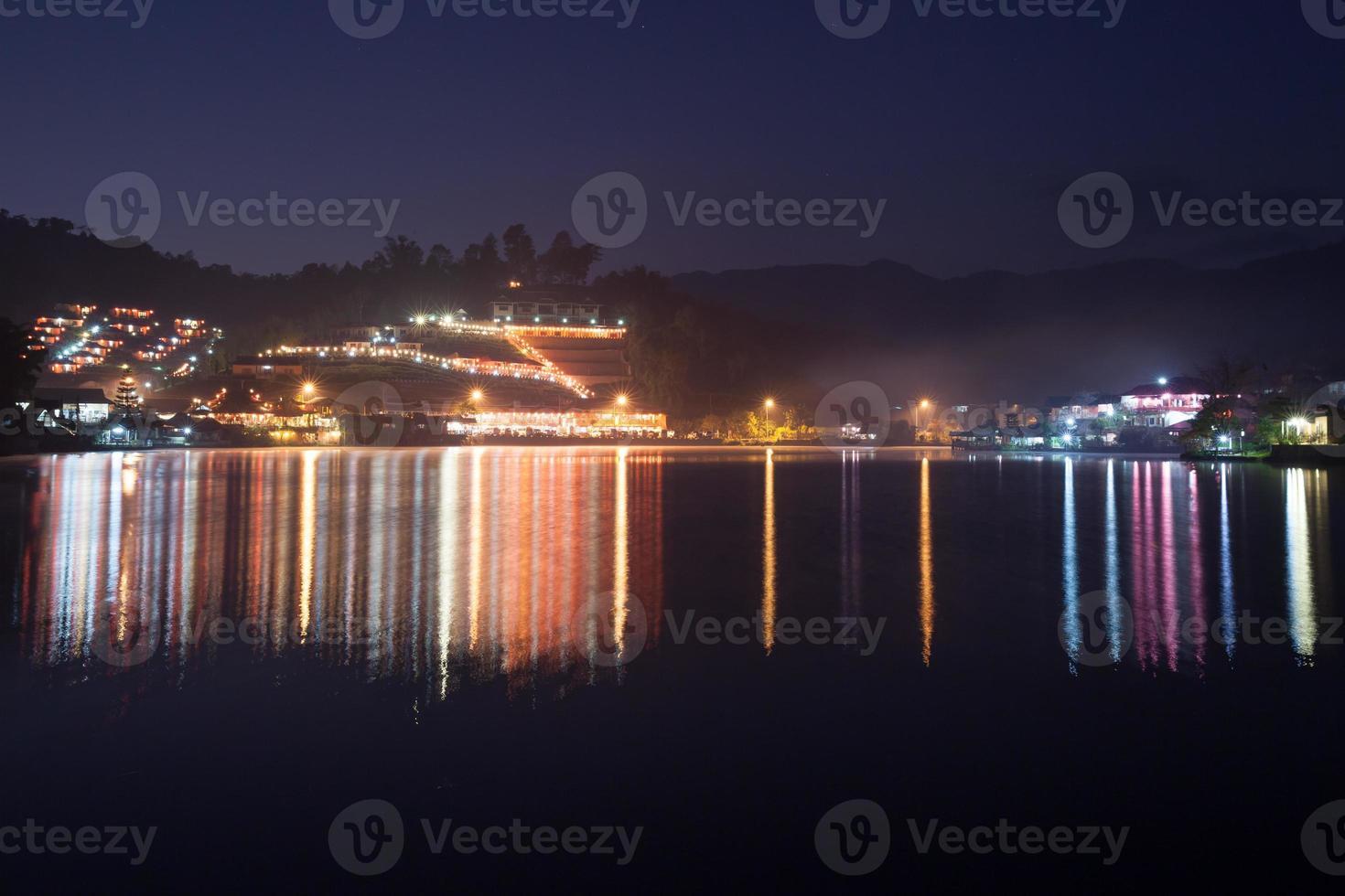 Reflejo de luces de pueblo colorido sobre el agua foto