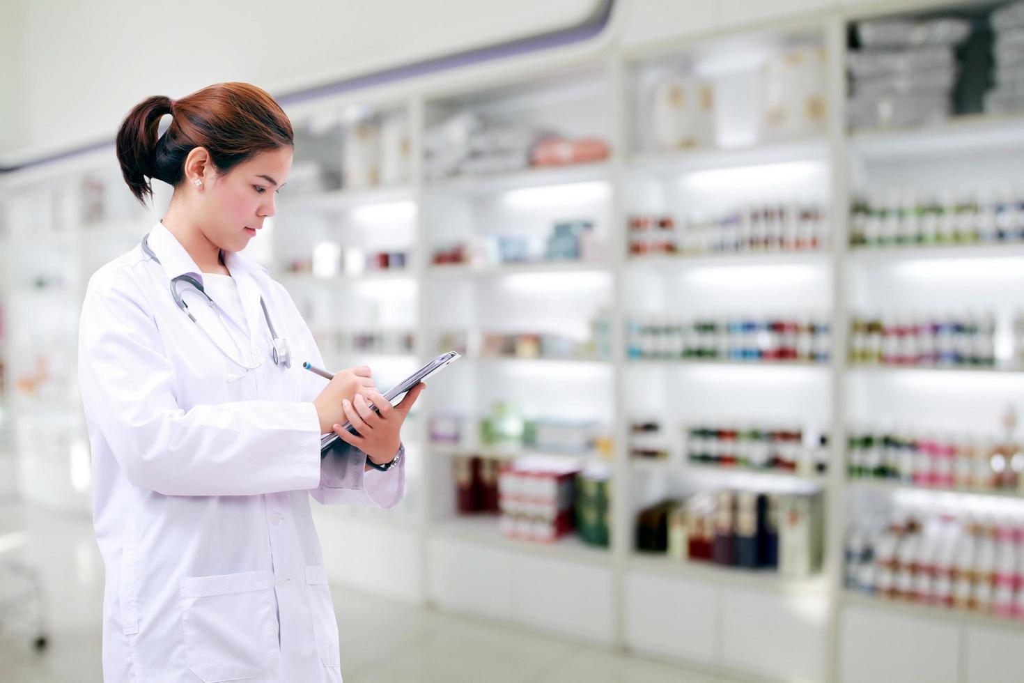 Mujer asiática farmacéutica en una farmacia foto