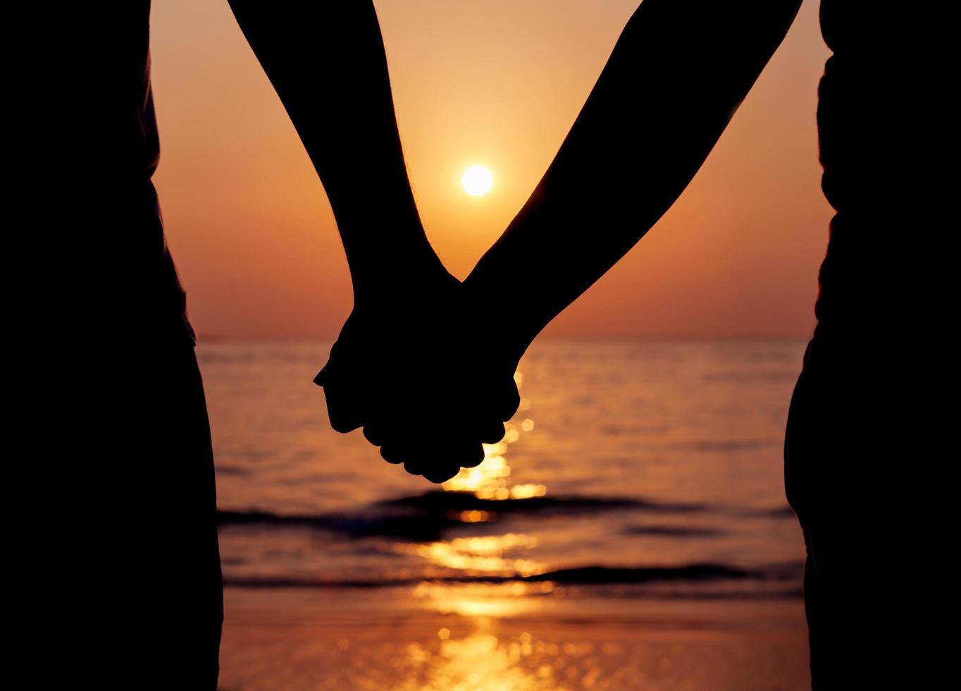 silueta de una pareja tomados de la mano al atardecer foto