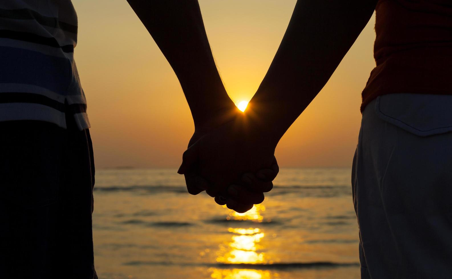 Couple holding hands at sunset photo