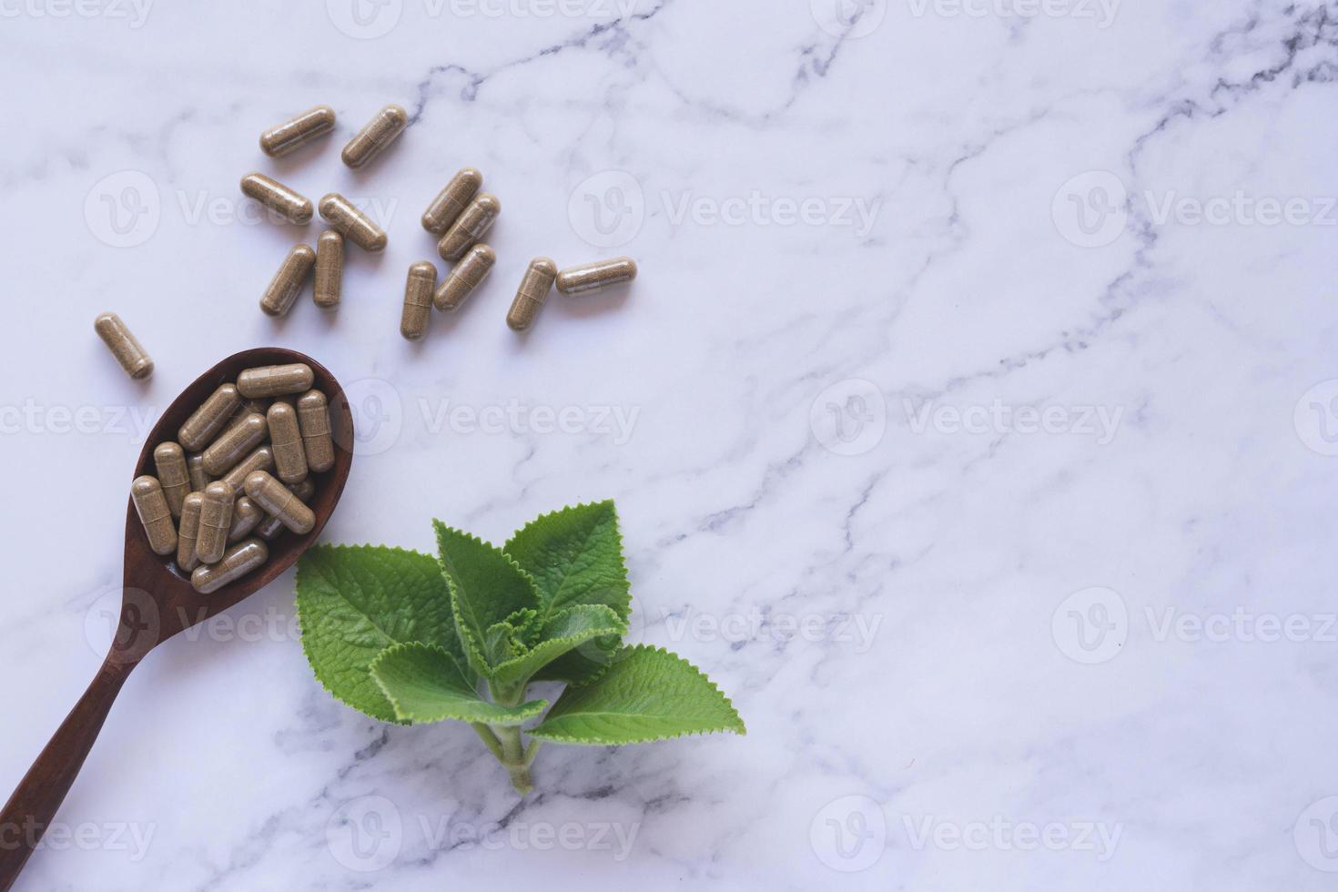 Medicina herbaria en cápsulas de mármol blanco. foto