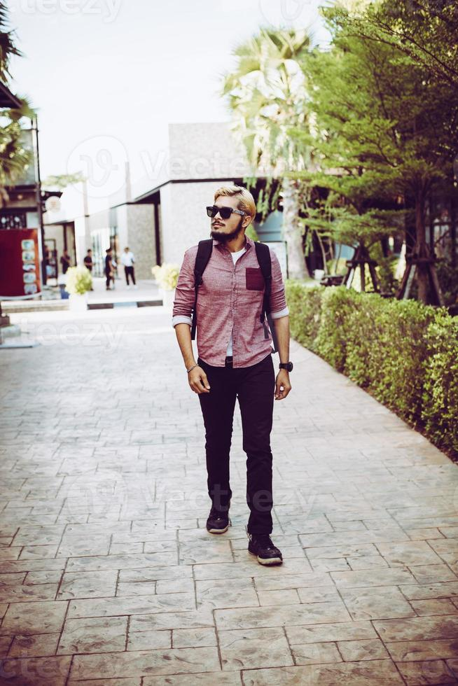 Retrato de hombre guapo hipster caminando por la calle foto