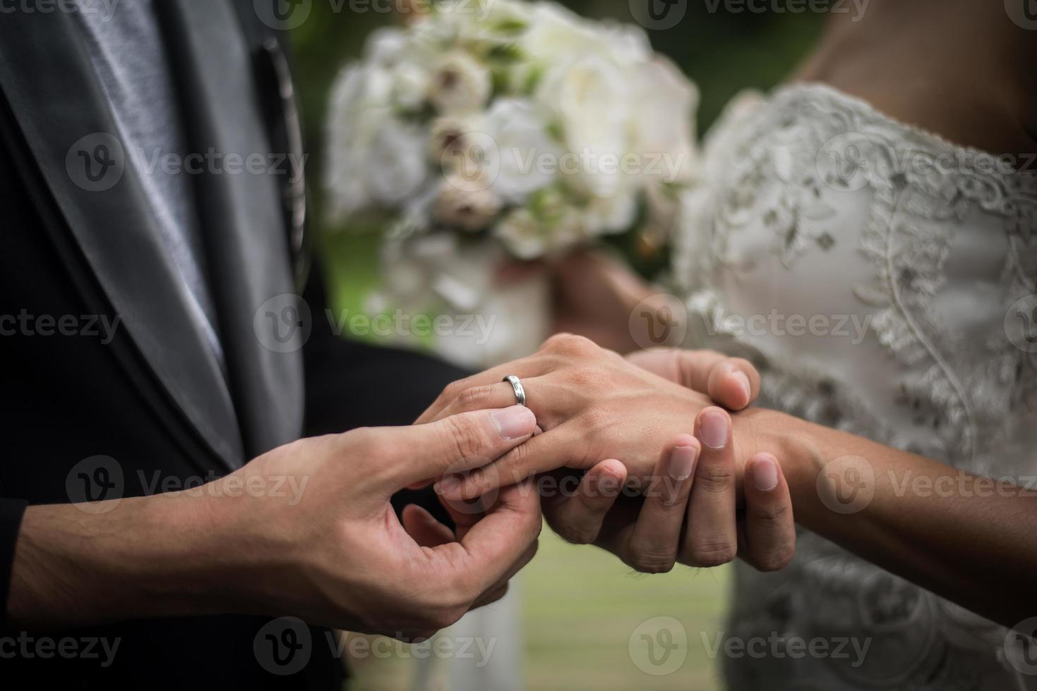 Close-up of groom putting ring on bride photo